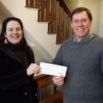 Jennifer Kirchoff of the Unitarian Universalist Church of Belfast and co-chairman of the annual Solstice Celebration, hands a check to John Arrison, treasurer of the Greater Bay Area Ministerium and its Interfaith Fuel Fund.